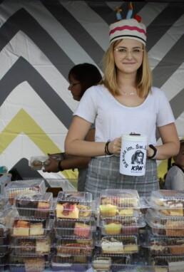 Zdjęcie, kobieta z puszką na. pieniądze przy stole z ciastem