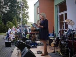 Zdjęcie, konferansjer zapowiadający koncert w tle instrumenty i publiczność