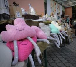 Zdjęcie, różowe poduszki w kształcie chmurki z nogami leżą na stoisku z rękodzielem