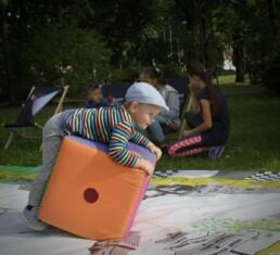Zdjęcie, chłopczyk opierający się o dużą kostkę do gry