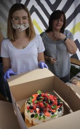Zdjęcie, dwie kobiety pokazują ciasto umieszczone w kartonie