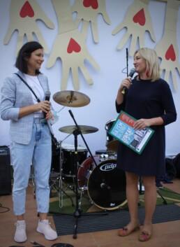 Zdjęcie, dwie kobiety. rozmawiające na scenie w trakcie koncertu