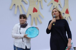 Zdjęcie, dwie kobiety na scenie; jedna mówi przez mikrofon, druga trzyma ozdobny talerz