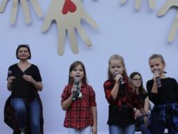 Zdjęcie, trzy śpiewające dziewczynki w trakcie występu, w tle reszta zespołu