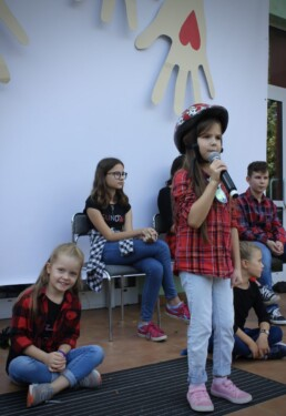 Zdjęcie, dziewczynka w trakcie śpiewania piosenki, w tle inni wokaliści