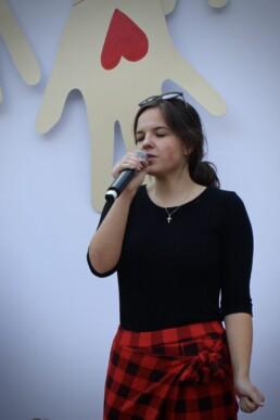 Zdjęcie, młoda dziewczyna śpiewa w trakcie koncertu