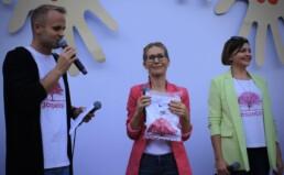 Zdjęcie, moment licytacji; kobieta trzymająca zapakowaną koszulkę i mężczyzna mówiący do mikrofonu