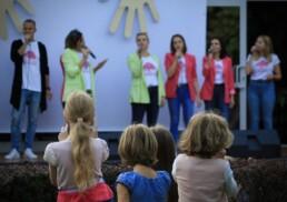 Zdjęcie, dzieci oglądające koncert; w tle śpiewający zespół