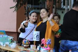 Zdjęcie, kobieta i dziewczyna pozujące przy straganie z rękodziełem