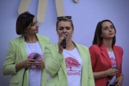 Zdjęcie, wokalistka w trakcie występu; w tle zespół
