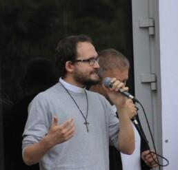 Zdjęcie, ksiądz śpiewający w trakcie występu z zespołem