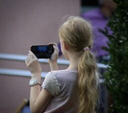 Zdjęcie, dziewczynka robiąca zdjęcie smartfonem, widok z tyłu