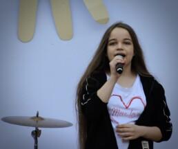 Zdjęcie, śpiewająca dziewczyna w trakcie występu