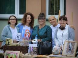 Zdjęcie, grupa kobiet pozująca przy stole pełnym rękodzieła
