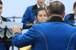 Zdjęcie, dyrygent orkiestry z perspektywy publiczności; w tle muzycy orkiestry