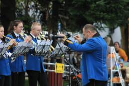 Zdjęcie, kapelmistrz dyrygujący muzykami orkiestry dętej
