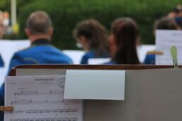 Zdjęcie, zapis nutowy w tle - orkiestra dęta