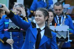 Zdjęcie, wokalistka kieruje mikrofon w stronę publiczności, w tle orkiestra dęta