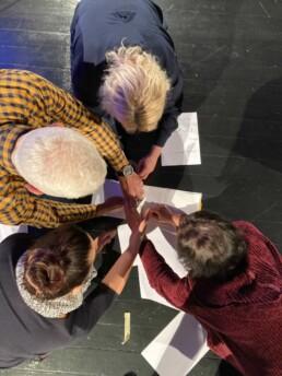 Zdjęcie, 4 uczestników szkolenia w trakcie wykonywania zadania; widok z góry