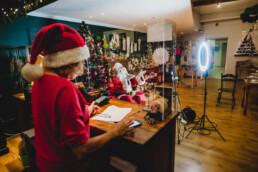 Zdjęcie, na pierwszym planie osoba w czapce Mikołaja stojąca tyłem do obiektywu, w tle Mikołaj w trakcie rozmowy przez smartfon