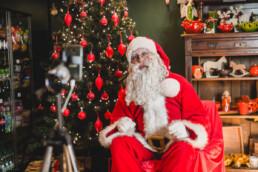Zdjęcie, święty Mikołaj ubrany w czerwony strój, siedzi na fotelu; w tle choinka z czerwonymi ozdobami i regał ze świątecznymi upominkami