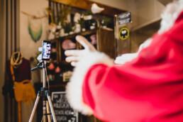 Zdjęcie, dłonie św. Mikołaja przed ekranem smartfona w trakcie rozmowy