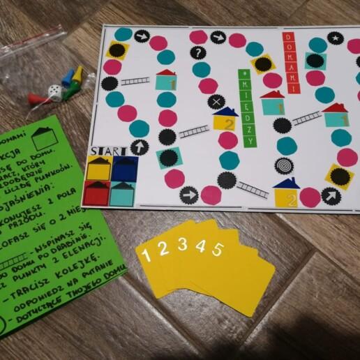 Zdjęcie; planszówka wykonana przez jednego z uczestników zajęć, kadr wypełnia plansza, zasady gry i 5 żółtych kart