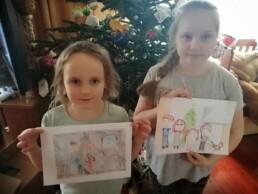 Zdjęcie, dwie dziewczynki trzymające w rękach swoje rysunki, na rysunkach - ich rodziny