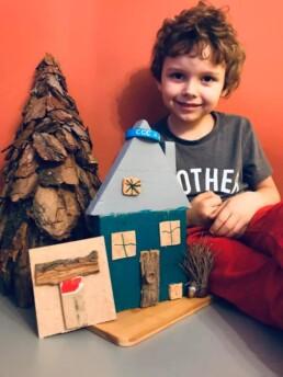 Zdjęcie, chłopiec prezentuje przygotowany przez siebie drewniany domek