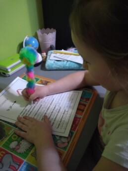Zdjęcie, dziewczynka siedząca przy biurku - wypełnia formularz, kadr z boku