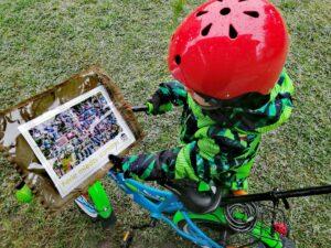 Zdjęcie, chłopczyk na rowerku przed sobą ma mapę miasta; kadr z góry