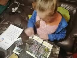 Zdjęcie, dziewczynka siedząca przy biurku, układająca z puzzli mapę miasta; kadr z góry