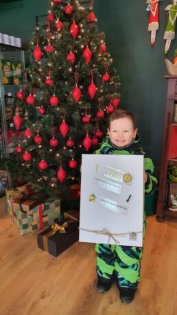 Zdjęcie, chłopiec ubrany w zimowy kombinezon stoi przy choince i prezentuje pudełko z napisem