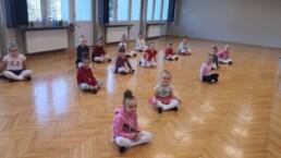 Zdjęcie_ Małe dziewczynki siedzą w siadzie skrzyżnym na drewnianej podłodze, na sali gimnastycznej.