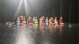 Zdjęcie_ Grupa taneczna małych dziewczynek siedzi na scenie. Przed sobą każda z nich ma małą poduszeczkę.