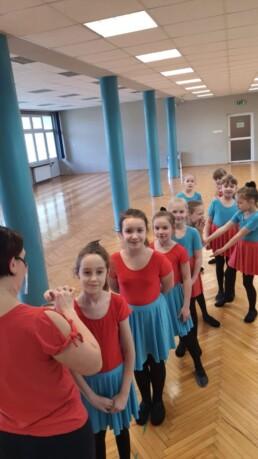 Zdjęcie_ Grupa taneczna małych dziewczynek stoi w kolejce na sali gimnastycznej. Z przodu stoi obrócona plecami kobieta, która trzyma w ręce puder i gąbeczkę.