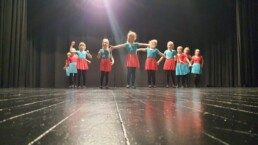 Zdjęcie_ Grupa taneczna małych dziewczynek stoi na scenie i wyciągają ręce szeroko.