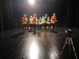 Zdjęcie_ Grupa taneczna dziewcząt tańczy na scenie. Na pierwszym planie w prawym dolnym rogu stoi statyw z kamerą.