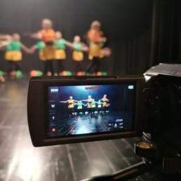 Zdjęcie_ Przybliżenie na ekran kamery, gdzie widać tańczącą grupę dziewczyn na scenie.