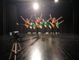 Zdjęcie_Grupa taneczna młodych dziewczyn tańczy na scenie. Prawe nogi mają podniesione w wysoko i ręce są wyciągnięte do góry. Kamera na statywie stoi w lewym dolnym rogu.