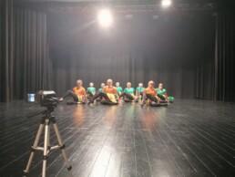 Zdjęcie_ Młode dziewczyny tańczą na scenie, siedzą i mają przełożoną lewą nogę. Na pierwszym planie po lewej stoi statyw z kamerą.