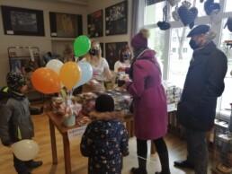 Zdjęcie_ Kobieta i mężczyzna z dwójką chłopców są ubrani na zimowo po lewej wazon z balonami na stole pudełka plastikowe z ciastami. Kobieta wrzuca pieniądze do puszki. Za ladą stoją dwie kobiety. W tle obrazy na ścianie.