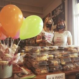 Zdjęcie_ Na stole plastikowe pudełka z ciastami. Po lewej w wazonie są bezowe lizaki i balony na patykach. Za stołem stoją dwie Panie w maseczkach, kobieta po lewej ma w ręku puszkę.