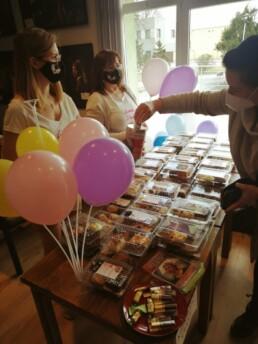 Zdjęcie_ Na stole pudełka plastikowe z ciastami i balony na patykach. Kobieta wrzuca pieniądze do puszki, która trzyma kobieta za ladą.